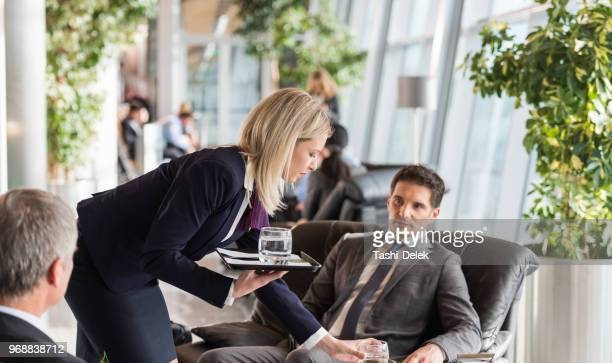 Airport Waitress Serving Coffee To Businessmen