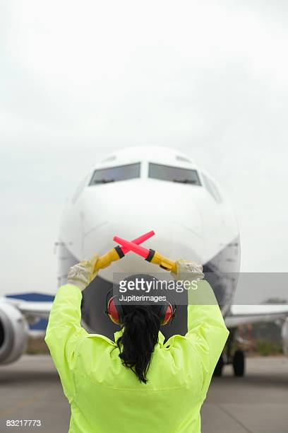 Airport worker directing jet