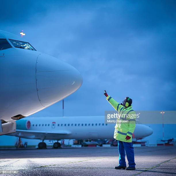 Airport worker guiding aircraft on runway at night