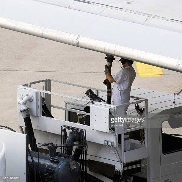 Airport worker refuelling an aeroplane before take off