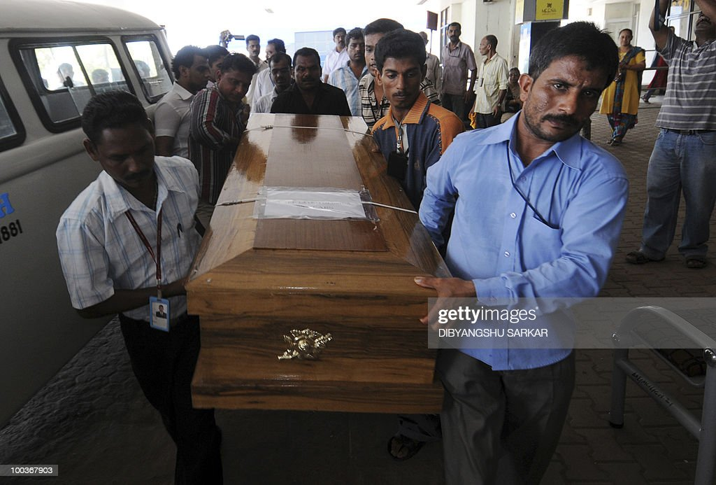Airport workers carry a coffin bearing the remains of pilot Zlapko Glusica, a British national of Serbian origin who was in command of the ill-fated Air India Express flight IX812, to be flown on a Delhi-bound flight in Mangalore on May 24, 2010. Investigators on May 22 widened the search for the 'black box' data recorder of an Air India Express that crashed into a gorge killing 158 people, as the airline denied lax safety claims. AFP PHOTO/Dibyangshu SARKAR