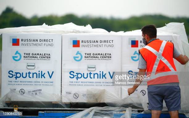 Airport workers handles containers on the runway after being unloaded from an Airbus 330-200 of Aerolineas Argentinas at Ministro Pistarini...