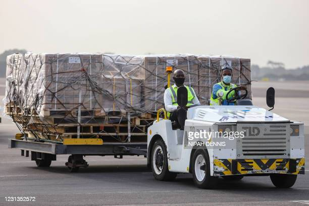 Airport workers transport on dollies a shipment of Covid-19 vaccines from the Covax global Covid-19 vaccination programme, at the Kotoka...