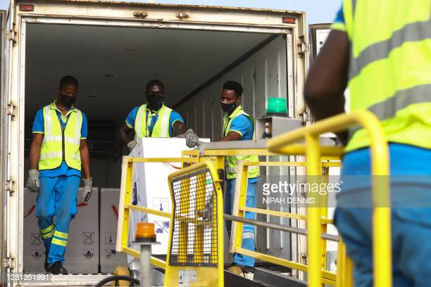 Airport workers unload a shipment of Covid-19 vaccines from the Covax global Covid-19 vaccination programme, at the Kotoka International Airport in...
