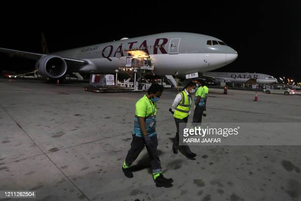 Airport workers wear maks as supplies to tackle the coronavirus COVID-19 pandemic donated by the Qatar Fund for Development are loaded onto a Qatar...