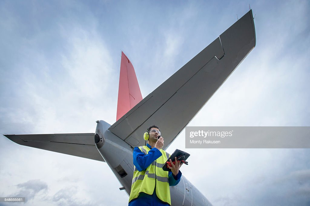 Airside engineer talking on radio near aircraft on runway, low angle view : Stock Photo
