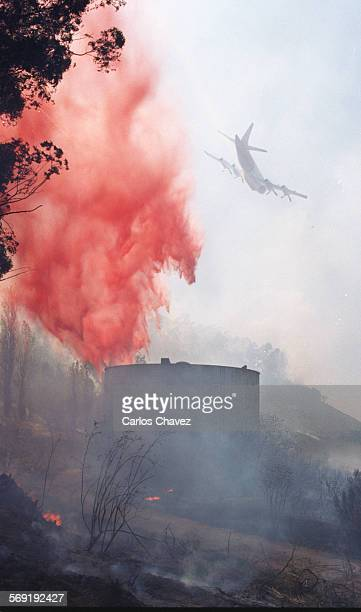 Airtanker drops retardent over a hot area on a hillside during a bursh fire in Somis