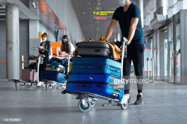 airtravelers at the airport with luggage, wearing n95 face masks - carrying stock pictures, royalty-free photos & images