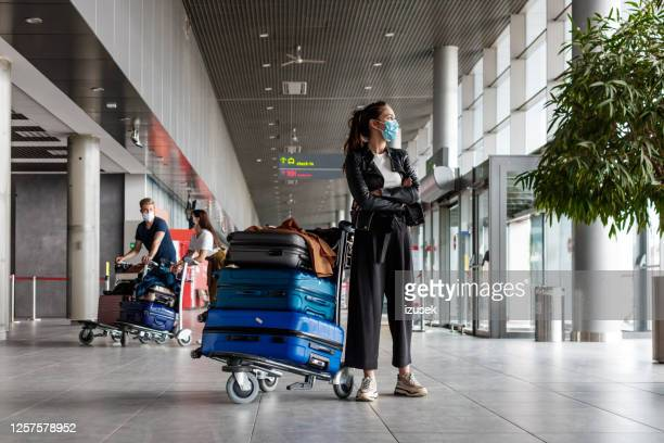 airtravelers at the airport with luggage, wearing n95 face masks - airport stock pictures, royalty-free photos & images