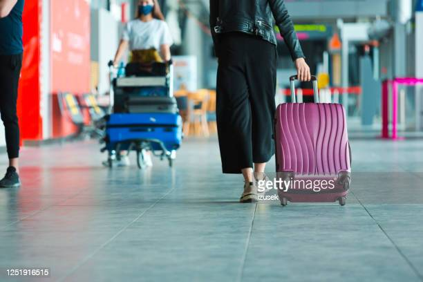 airtravellers at the airport carrying luggage - airport stock pictures, royalty-free photos & images