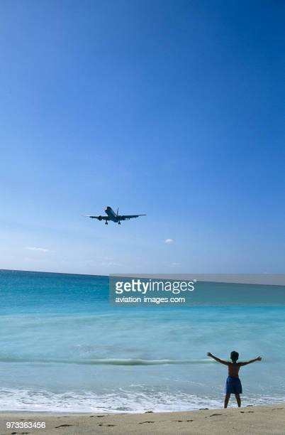 Airways Boeing 757-200 on very low final-approach landing over Maho Beach with boy child standing on beach waving.