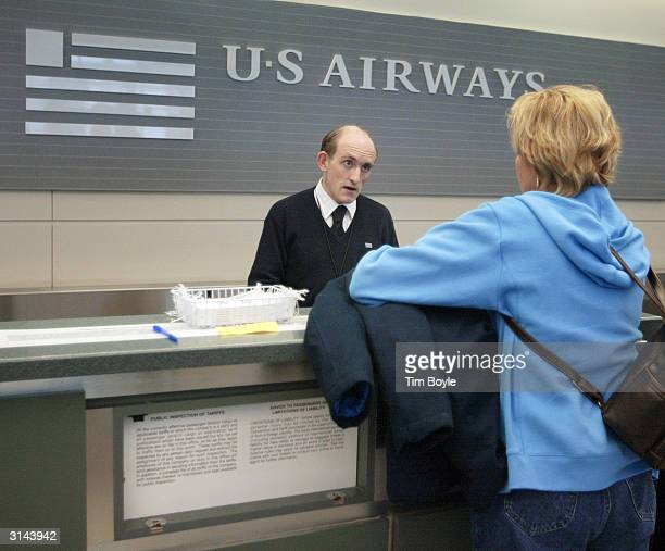 Airways customer service agent William Farrell assists a traveler at the US Airways ticket counter at Midway Airport March 26 2004 in Chicago...