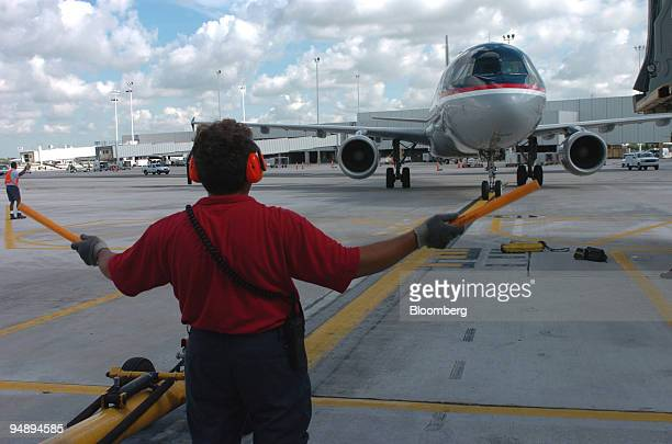 Airways ground crew member guides an Airbus 321 to the gate at Fort LauderdaleHollywood Florida International Airport Monday August 23 2004 US...