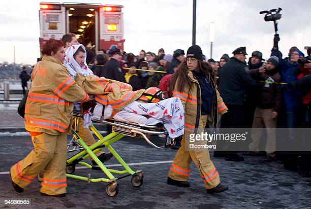 Airways Group Inc passenger is taken away on a stretcher near a crash site in the Hudson River in New York US on Thursday Jan 15 2009 The jetliner...