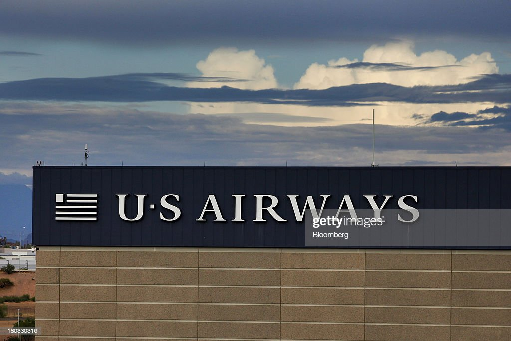 US Airways Group Inc. signage is displayed on the company's building at Phoenix Sky Harbor International Airport (PHX) in Phoenix, Arizona, U.S., on Sunday, Sept. 8, 2013. Yields on benchmark securities climbed to almost two-year highs as consumers spent more on travel and tourism while manufacturing expanded modestly from early July through late August, according to the Federal Reserves Beige Book. Photographer: Patrick T. Fallon/Bloomberg via Getty Images
