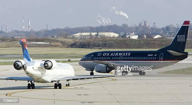 Airways jet and a Delta Connection jet taxi on the tarmac at the Philadelphia International Airport November 15 2006 in Philadelphia Pennsylvania US...