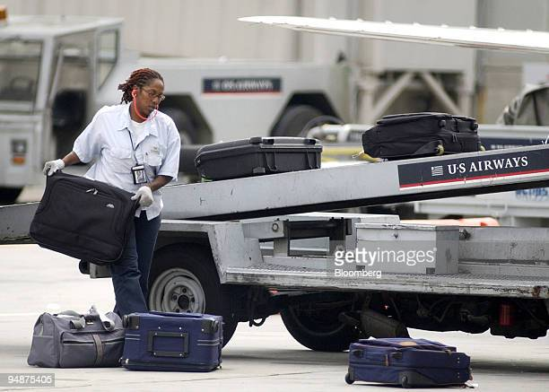 Airways worker unloads baggage from an airplane at Philadelphia International Airport in Philadelphia Pennsylvania Thursday September 14 2004 US...