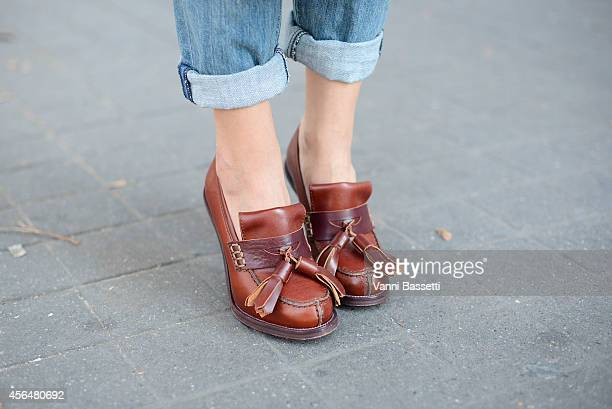 Aisha Baker poses wearing Current Elliot pants and Acne shoes on the streets of Paris during Paris fashion week on October 1 2014 in Paris France