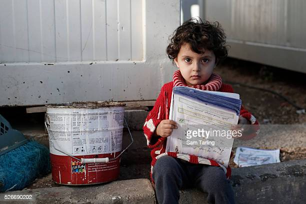 Aisha Nour from Azaz Syria reads outside the container in which she and her family live at the 'Container City' refugee camp at Oncupinar Turkey near...