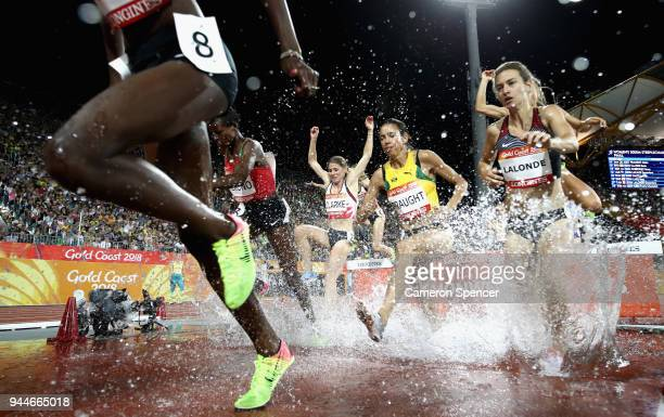 Aisha Praught of Jamaica and Genevieve Lalonde of Canada clear the water jump competes in the Women's 3000 metres Steeplechase final during athletics...