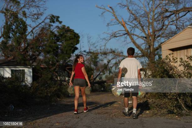 Aisha Roldan and her brother Anthony Roldan carry jugs of water from a nearby body of water to use to flush the toilets at their house after...