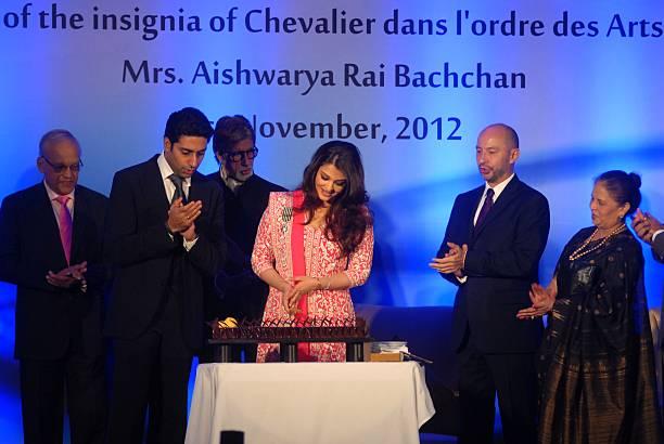 Aishwarya Rai Bachchan cutts a cake as her husband Abhishek Bachchan father in law Amitabh Bachchan father Krishna Rai mother Brindya Rai and French..