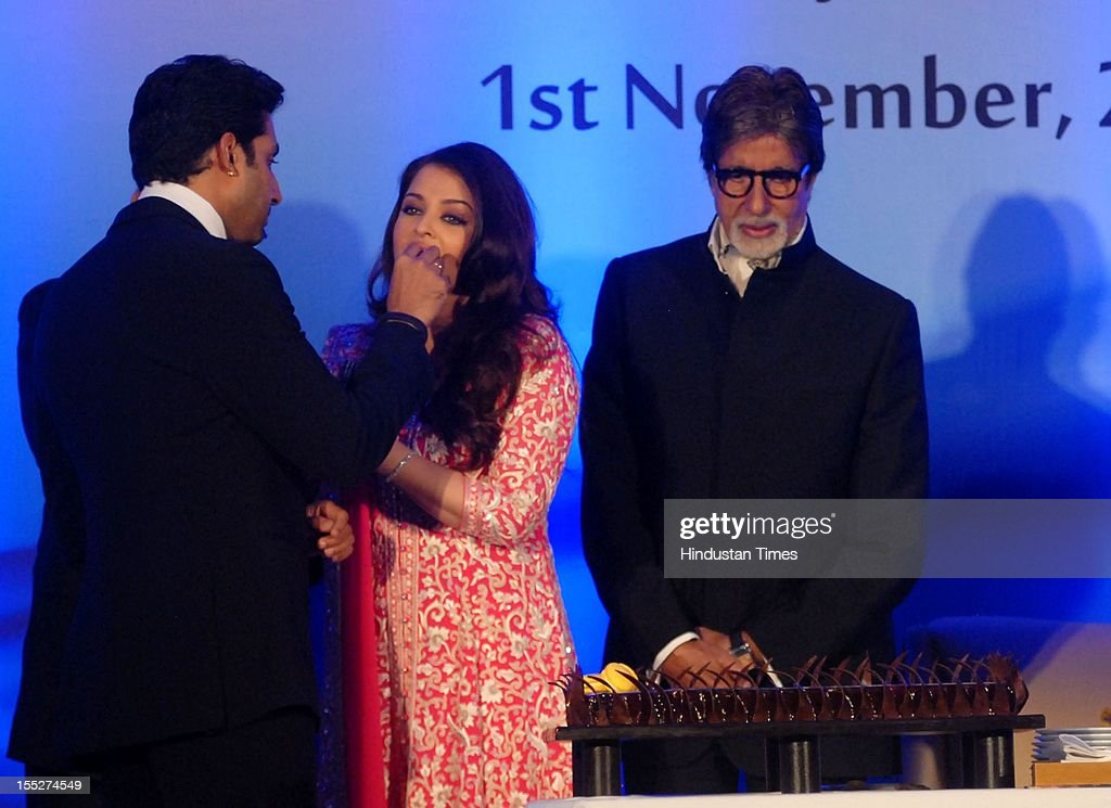 Aishwarya Rai Bachchan is fed cake by her husband Abhishek Bachchan as Amitabh Bachchan looks on during a function to confer her with French Knight...