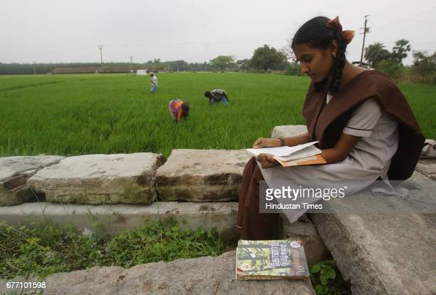 Aishwarya studies for her Tenth Boards from her anthology of Tamil classics in salwar kameez school uniform while her brother Ram Kumar and his field...