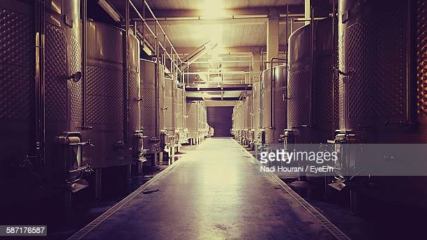aisle amidst storage tanks in brewery - brewery stock pictures, royalty-free photos & images