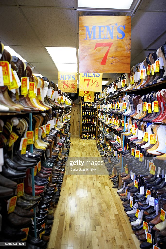 Aisle lined with cowboy boots in shoe store : Stock Photo