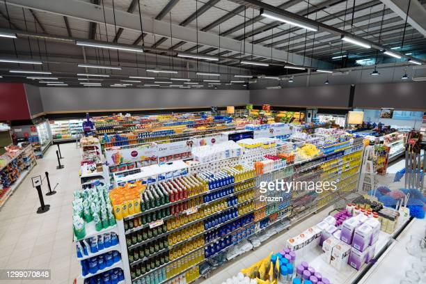 aisles and shelves in supermarket, wide angle view - supermarket stock pictures, royalty-free photos & images