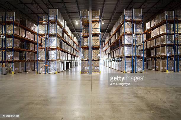 aisles in warehouse - lagerhalle stock-fotos und bilder