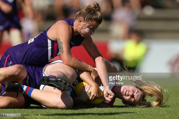 Aisling McCarthy of the Bulldogs gets tackled by Kiara Bowers and Kellie Gibson of the Dockers during the round five AFLW match between the Fremantle...