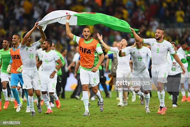 Aissa Mandi Madjid Bougherra and Nabil Ghilas of Algeria carry a flag in celebration after a 11 draw during the 2014 FIFA World Cup Brazil Group H...