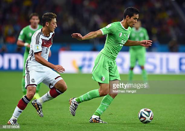 Aissa Mandi of Algeria controls the ball as Mesut Oezil of Germany gives chase during the 2014 FIFA World Cup Brazil Round of 16 match between...