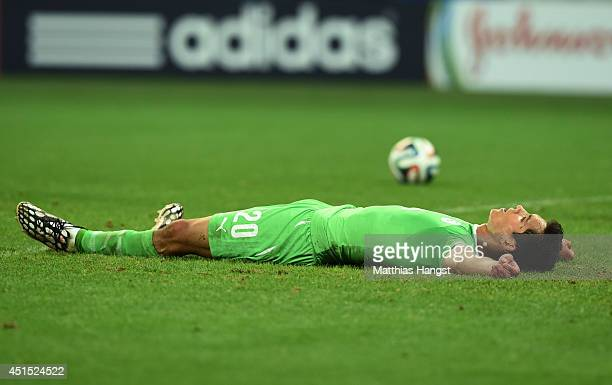 Aissa Mandi of Algeria lies on the field after a goal by Germany in extra time during the 2014 FIFA World Cup Brazil Round of 16 match between...