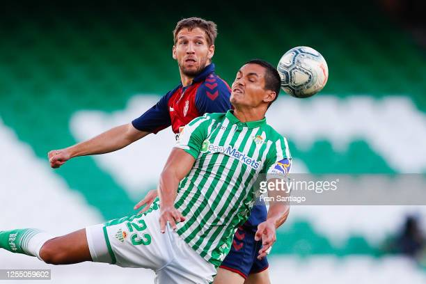 Aissa Mandi of Real Betis Balompie competes for the ball with Darko Brasanac of CA Osasuna during the Liga match between Real Betis Balompie and CA...