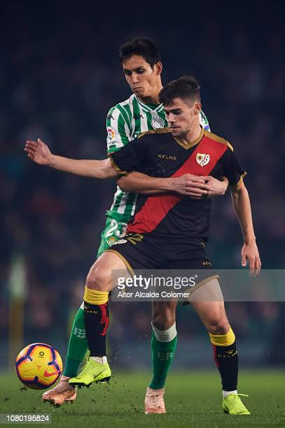 Aissa Mandi of Real Betis Balompie competes for the ball with Jose Angel Pozo of Rayo Vallecano during the La Liga match between Real Betis Balompie...