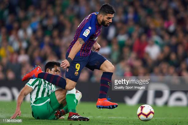 Aissa Mandi of Real Betis Balompie competes for the ball with Luis Suarez of FC Barcelona during the La Liga match between Real Betis Balompie and FC...