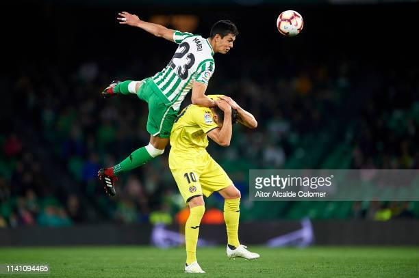 Aissa Mandi of Real Betis Balompie competes for the ball with Vicente Iborra of Villarreal CF during the La Liga match between Real Betis Balompie...