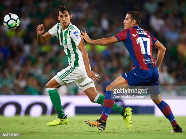 Aissa Mandi of Real Betis Balompie is pursued by Alex Alegria of Levante UD during the La Liga match between Real Betis and Levante at Estadio Benito...