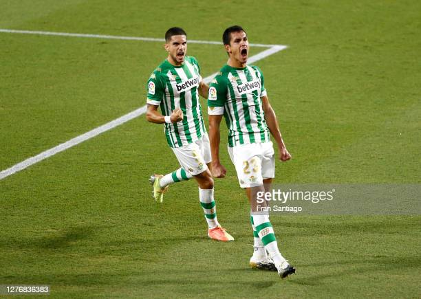 Aissa Mandi of Real Betis celebrates with teammate Marc Bartra after scoring his team's first goal during the La Liga Santader match between Real...