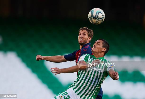 Aissa Mandi of Real Betis competes for the ball with Brasanac of CA Osasuna during the Liga match between Real Betis Balompie and CA Osasuna at...