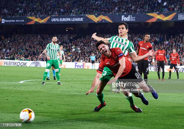 Aissa Mandi of Real Betis duels for the ball with Clement Grenier of Stade Rennais during the UEFA Europa League Round of 32 Second Leg match between...