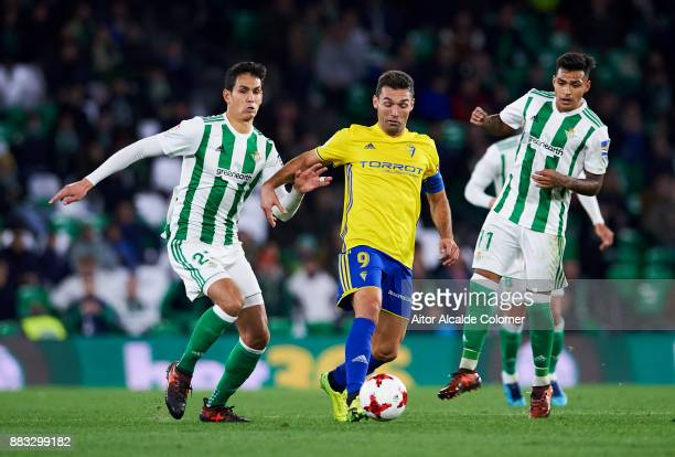 Aissa Mandi of Real Betis duels for the ball with David Barral of Cadiz during the Copa del Rey Round of 32 Second Leg match between Real Betis...