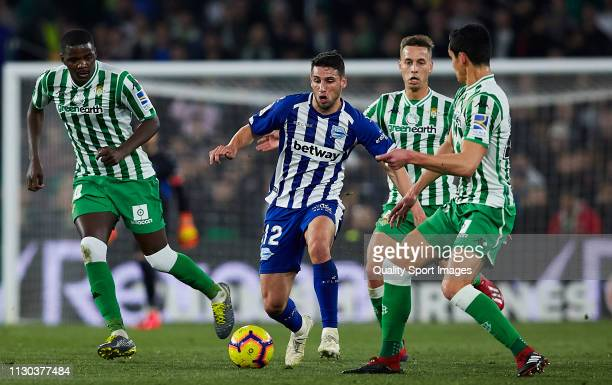 Aissa Mandi William Carvalho Sergio Canales of Real Betis competes for the ball with Calleri of Deportivo Alaves during the La Liga match between...