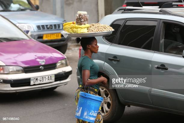 Aisssatou Ba Bourkinabe a young peanuts street vendor walks through traffic in Libreville on June 25 2018 Bought in West Africa hundreds of child...