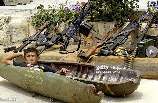 A Lebanese boy relaxes 15 July 2007 inside a shell dropped by Israeli warplanes during last year's summer war displayed in the southern village of...