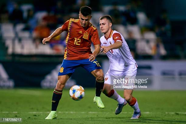 Aitor Bunuel of Spain competes for the ball with Alija Krnic of Montenegro during the UEFA European Under-21 Championship Qualifying between Spain...