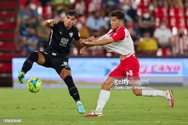 Aitor Bunuel of UD Almeria competes for the ball with Kevin of Malaga CF during the Liga Smartbank match betwen UD Almeria and Malaga CF at Municipal...